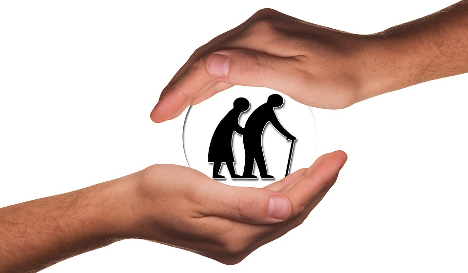 Image of elderly couple in a globe being held between right and left hands