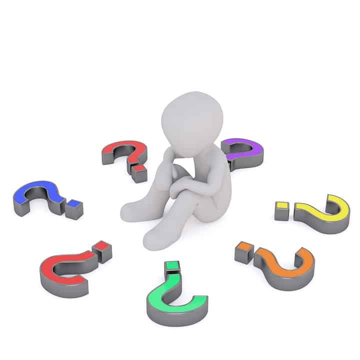 Image of a Cartoon man setting inside a circle of Question Marks that are laying flat