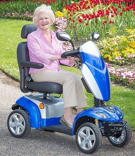 An elderly woman riding a senior citizen scooter