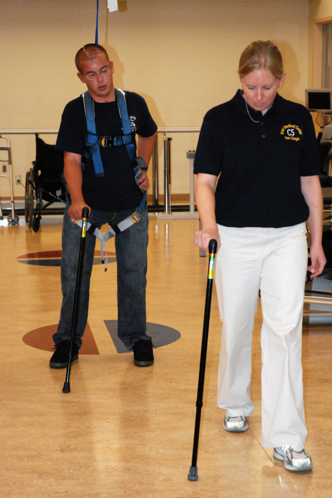 Image of a woman with a cane teaching a man to walk with a cane.