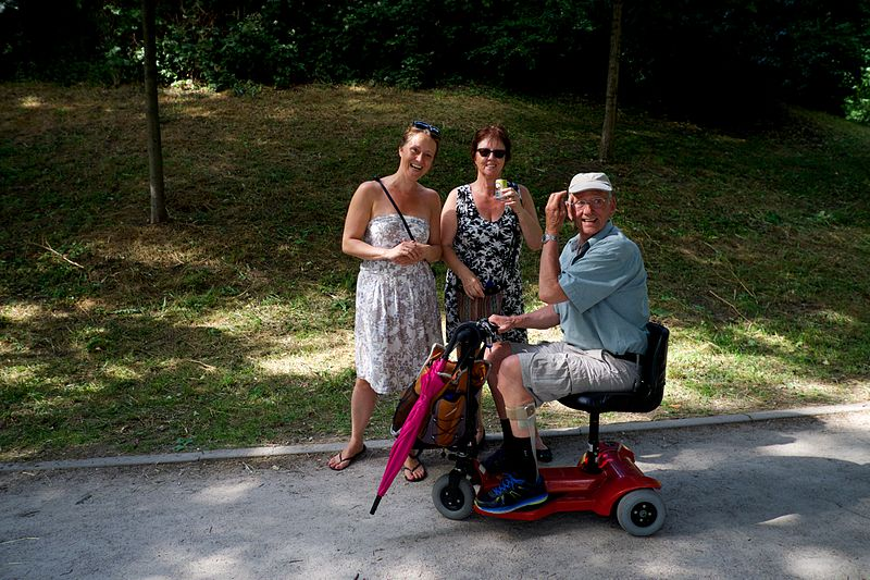 Image of an older man on a scooter with family members, on a tour.