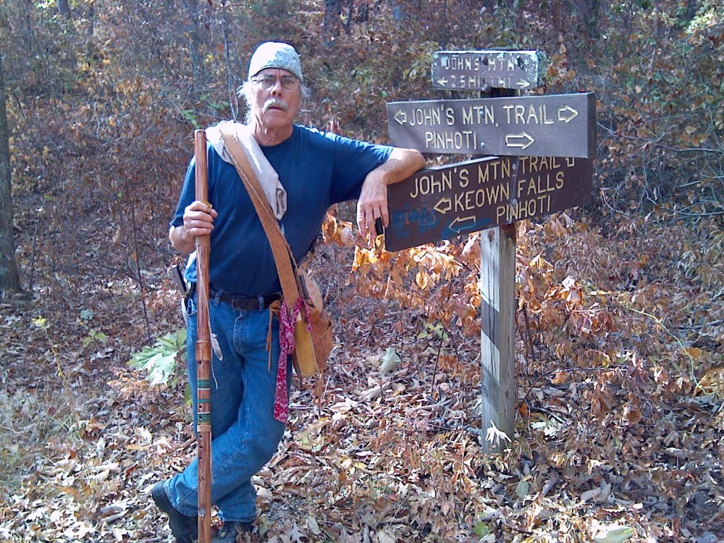 Image of an elderly man with a hiking stick leaning on a group of hiking trail signs