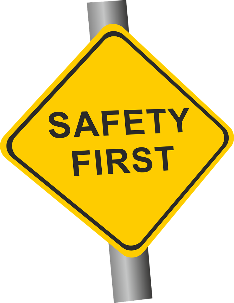 Image of a yellow diamond shaped sign stating safety first.