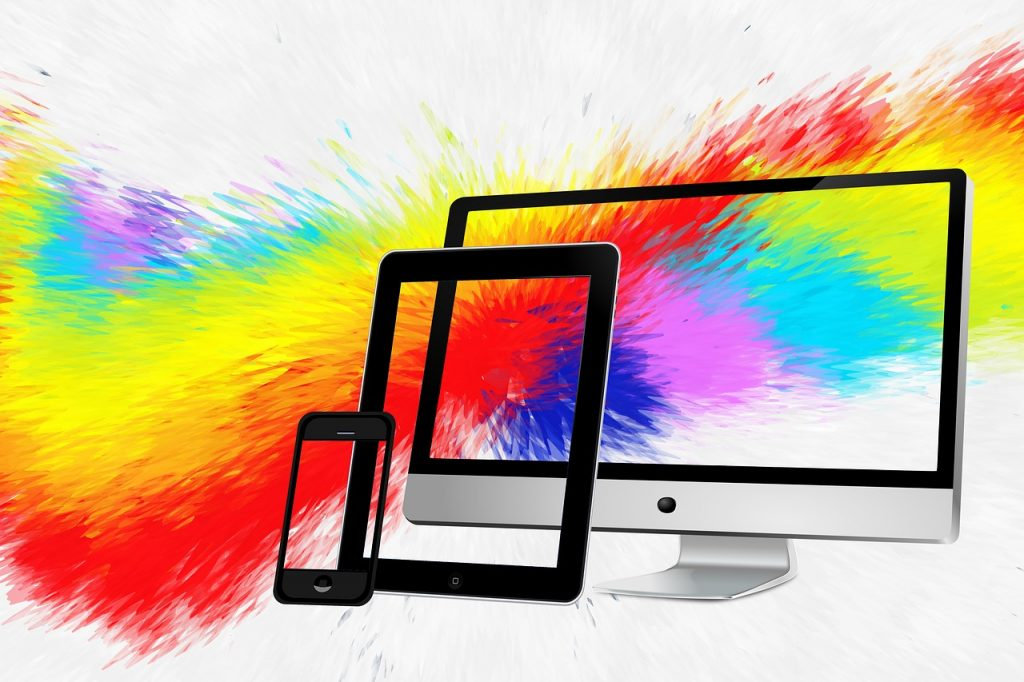 Image of a rainbow of colors strewn across phone, tablet, and monitor screens