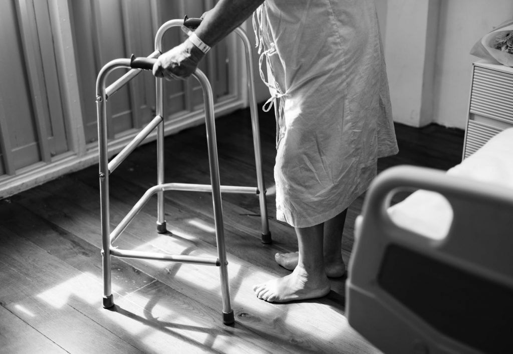 Image of elderly person walking away from bed with walker