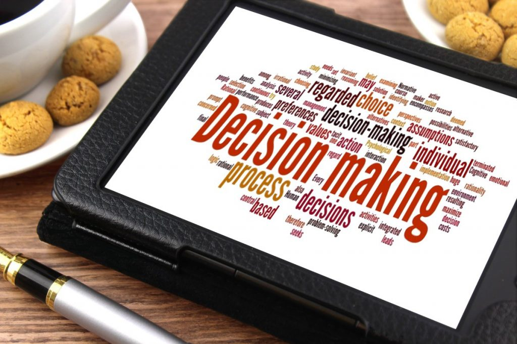 "Image of a tablet with the words ""decision making"" in the big letters in the center of the tablet"