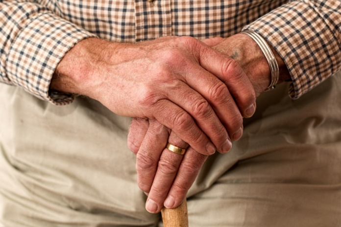 Elderly man's hands rest on a cane