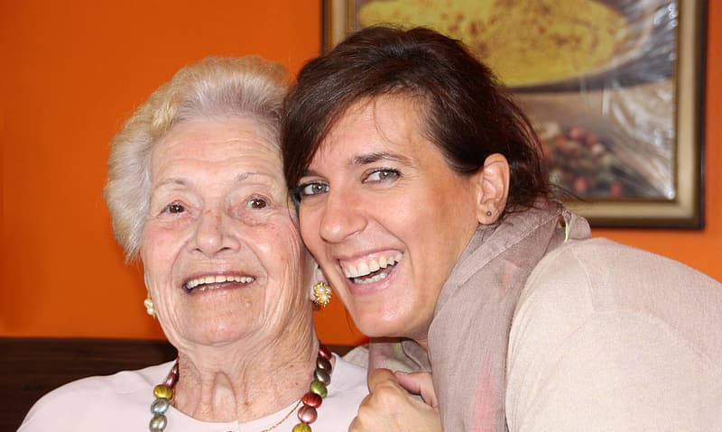 Image of an elderly woman being hugged by a younger woman, both smiling.