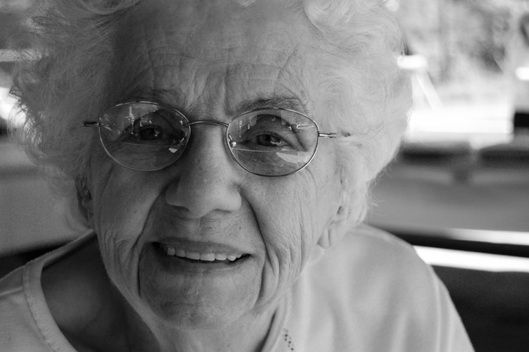 Image of a senior lady with glasses smiling at you